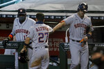 Houston Astros' Jose Altuve (27) is greeted by teammate Josh Reddick and manager Dusty Baker Jr., left, after scoring on a base hit by Yuli Gurriel during the fourth inning of a baseball game against the Arizona Diamondbacks Thursday, Aug. 6, 2020, in Phoenix. (AP Photo/Matt York)