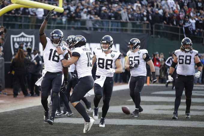 Jacksonville Jaguars wide receiver Chris Conley (18) is greeted by quarterback Gardner Minshew (15) after scoring a touchdown late in the second half of an NFL football game against the Oakland Raiders in Oakland, Calif., Sunday, Dec. 15, 2019. Jacksonville won the game 20-16. (AP Photo/Ben Margot)