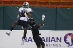 Nevada wide receiver Tory Horton (20) pulls in a touchdown pass over Hawaii defensive back Michael Washington (21) during the second half of an NCAA college football game Saturday, Nov. 28, 2020, in Honolulu. (AP Photo/Marco Garcia)