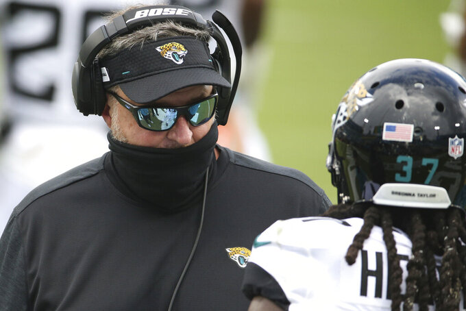 Jacksonville Jaguars head coach Doug Marrone, left, talks with cornerback Tre Herndon during timeout in the first half of an NFL football game against the Indianapolis Colts, Sunday, Sept. 13, 2020, in Jacksonville, Fla. (AP Photo/Stephen B. Morton)