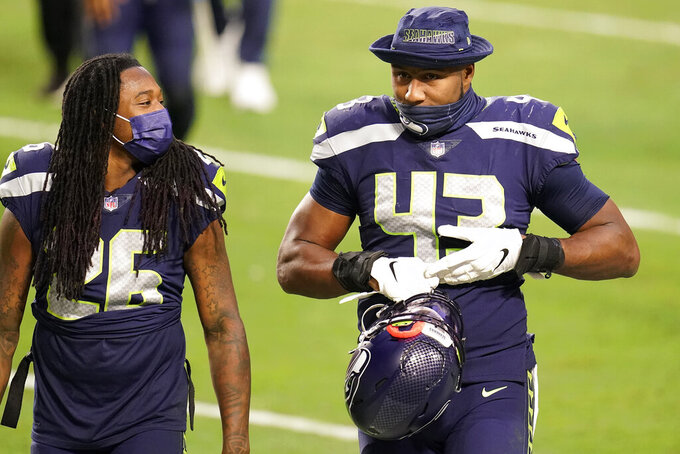 Seattle Seahawks defensive end Carlos Dunlap (43) leave the field with cornerback Shaquill Griffin (26) after an NFL football game against the San Francisco 49ers, Sunday, Jan. 3, 2021, in Glendale, Ariz. The Seahawks won 26-23. (AP Photo/Ross D. Franklin)