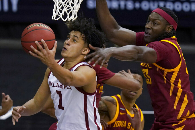 Oklahoma forward Jalen Hill (1) gets past Iowa State forward Solomon Young (33) during the first half of an NCAA college basketball game in the first round of the Big 12 men's tournament in Kansas City, Mo., Wednesday, March 10, 2021. (AP Photo/Orlin Wagner)