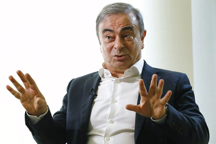 FILE - In this Jan. 10, 2020, file photo, former Nissan Chairman Carlos Ghosn speaks to Japanese media during an interview in Beirut, Lebanon. Two men wanted by Japan for helping sneak Ghosn out of the country in a box are due back in front of a Boston federal judge on Tuesday, July 28, 2020, to argue for their release from jail. (Meika Fujio/Kyodo News via AP)