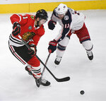Chicago Blackhawks left wing Brendan Perlini (11) and Columbus Blue Jackets right wing Cam Atkinson (13) fight for the puck during the second period of an NHL hockey game Saturday, Feb. 16, 2019, in Chicago. (AP Photo/Matt Marton)