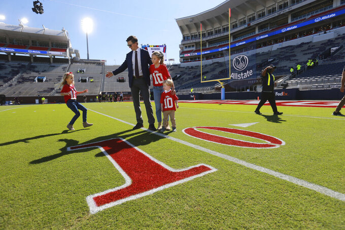 """Former Mississippi quarterback Eli Manning and his children get together for a photograph around the """"10"""" yard mark that has been painted red in his honor at Jerry Hollingsworth Field in Oxford, Miss., Saturday, Oct. 23, 2021. The school will retire his number during a halftime ceremony of an NCAA college football game against LSU. (Thomas Wells/The Northeast Mississippi Daily Journal via AP)"""