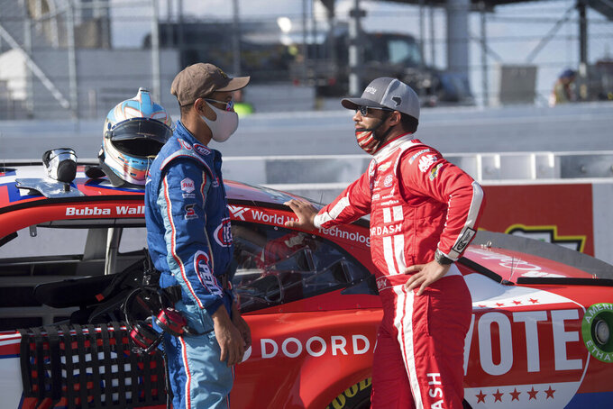 Bubba Wallace (43), rights talks to a crew member before a NASCAR Cup Series auto race at the Martinsville Speedway in Martinsville, Va., Sunday, Nov.1, 2020. (AP Photo/Lee Luther Jr.)