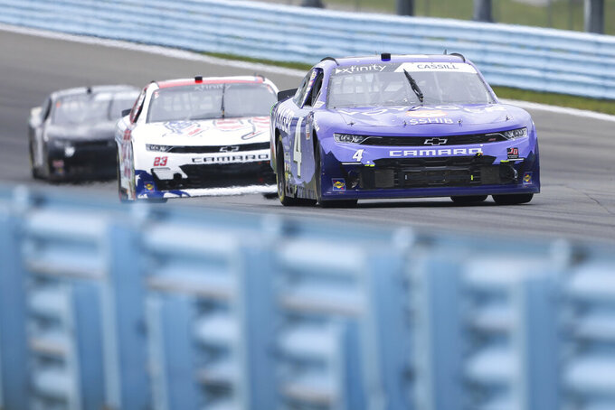 Landon Cassill (4) drives ahead of Austin Dillons, center, through the Esses in the NASCAR Xfinity Series auto race at Watkins Glen International in Watkins Glen, N.Y., on Saturday, Aug. 7, 2021. (AP Photo/Joshua Bessex)