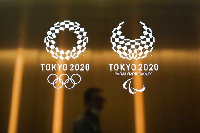 "FILE - In this June 11, 2019, file photo, a man walks past the Tokyo 2020 Olympic logos in Tokyo. One of the creative directors for this year's Tokyo Olympics has resigned following allegations of what are being termed ""power harassment."" Kaoru Sugano stepped away from the position and his resignation has been confirmed by the Tokyo organizing committee. (AP Photo/Jae C. Hong, File)"