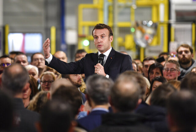 French President Emmanuel Macron delivers a speech as he visits a plant of British-Swedish pharmaceutical group Astrazeneca in Dunkirk, northern France, Monday, Jan. 20, 2020. French President Emmanuel Macron is hosting 180 international business leaders later today at the Palace of Versailles in a bid to promote France's economic attractiveness despite over six weeks of crippling strikes over his government's planned pension changes.(Denis Charlet/Pool Photo via AP)