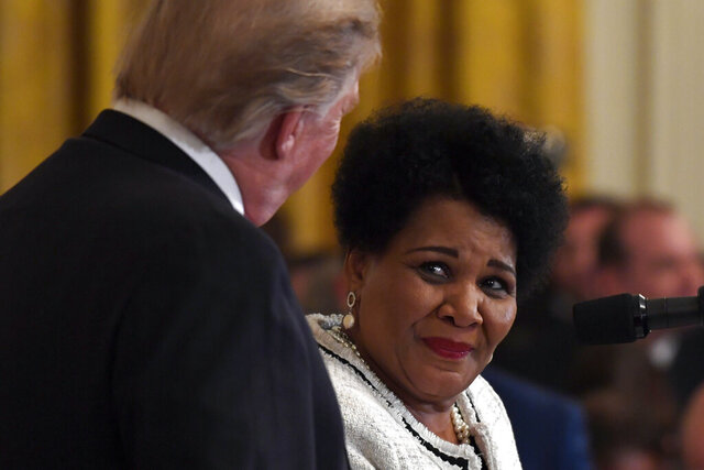 FILE - In this April 1, 2019, file photo President Donald Trump, left, listens as former prisoner Alice Marie Johnson, right, speaks at the 2019 Prison Reform Summit and First Step Act Celebration in the East Room of the White House in Washington. The 64-year-old African American great-grandmother spent 21 years in prison for a nonviolent drug offense before Trump commuted her sentence in 2018. (AP Photo/Susan Walsh, File)