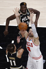 Chicago Bulls' Nikola Vucevic (9) defends against the shot of Atlanta Hawks' Trae Young (11) during the first half of an NBA basketball game Friday, April 9, 2021, in Atlanta. (AP Photo/Ben Margot)