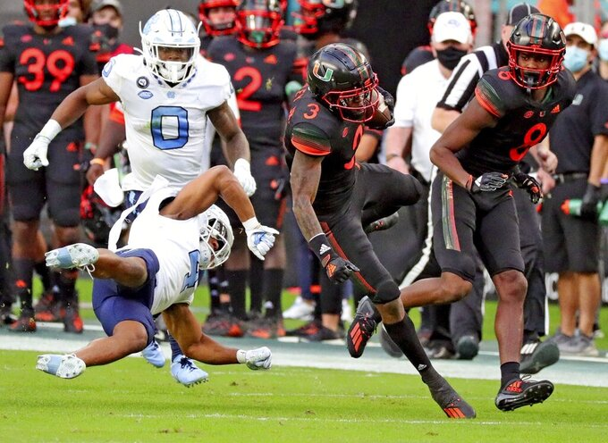 Miami wide receiver Mike Harley (3) runs with the ball after a reception as North Carolina defensive back Trey Morrison (4) defends during the first half of an during an NCAA college football game at Hard Rock Stadium In Miami Gardens, Fla, Saturday, Dec, 12, 2020. (Al Diaz/Miami Herald via AP)