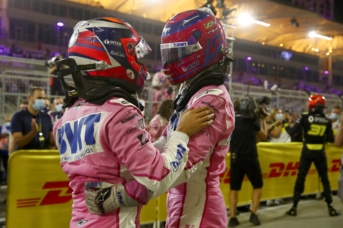 Racing Point driver Sergio Perez of Mexico, left, celebrates with his team mate Lance Stroll of Canada after he won the Formula One Bahrain Grand Prix in Sakhir, Bahrain, Sunday, Dec.6, 2020. (Brynn Lennon, Pool via AP)