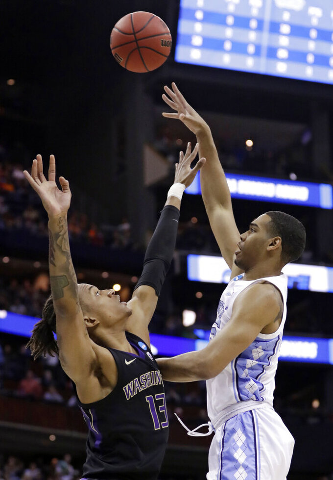 North Carolina's Garrison Brooks, right, shoots over Washington's Hameir Wright in the first half during a second round men's college basketball game in the NCAA Tournament in Columbus, Ohio, Sunday, March 24, 2019. (AP Photo/Tony Dejak)