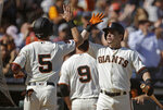 San Francisco Giants' Mike Yastrzemski (5) is congratulated by Scooter Gennett, right, after scoring against the Philadelphia Phillies in the first inning of a baseball game Sunday, Aug. 11, 2019, in San Francisco. (AP Photo/Ben Margot)