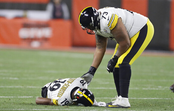 Pittsburgh Steelers offensive guard Ramon Foster (73) helps wide receiver JuJu Smith-Schuster (19) after an injury during the first half of the team's NFL football game against the Cleveland Browns, Thursday, Nov. 14, 2019, in Cleveland. (AP Photo/Ron Schwane)