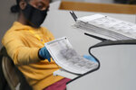 FILE - In this Nov. 5, 2020, file photo a county election worker scans mail-in ballots at a tabulating area at the Clark County Election Department in Las Vegas. The Nevada Secretary of State's office said voters do not lose their eligibility to vote or void their registration when they leave the state temporarily, even for long periods of time and may travel for 30 days or more and still cast a ballot. (AP Photo/John Locher, File)