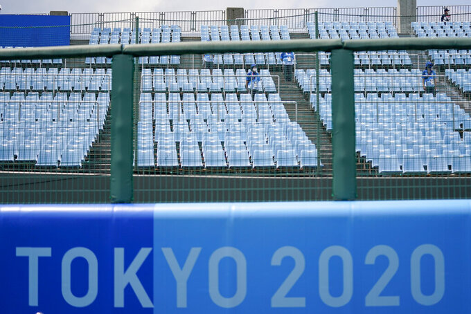 Games staff sit in the empty stands during the softball game between the Mexico and Japan at the 2020 Summer Olympics, Thursday, July 22, 2021, in Fukushima , Japan. (AP Photo/Jae C. Hong)