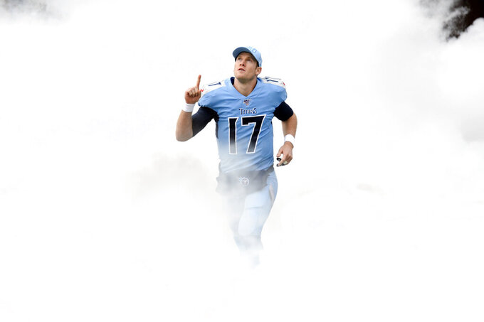Tennessee Titans quarterback Ryan Tannehill runs through smoke as he is introduced before an NFL football game between the Titans and the Houston Texans Sunday, Dec. 15, 2019, in Nashville, Tenn. (AP Photo/Mark Zaleski)