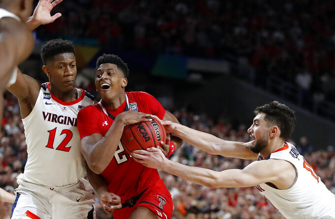 Texas Tech's Jarrett Culver (23) drives against Virginia's Ty Jerome (11) and De'Andre Hunter (12) during the overtime in the championship of the Final Four NCAA college basketball tournament, Monday, April 8, 2019, in Minneapolis. (AP Photo/Jeff Roberson)
