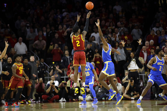 Southern California guard Jonah Mathews (2) makes a game-winning 3-point basket over UCLA forward Jalen Hill as time expires during the second half of an NCAA college basketball game Saturday, March 7, 2020, in Los Angeles. (AP Photo/Marcio Jose Sanchez)