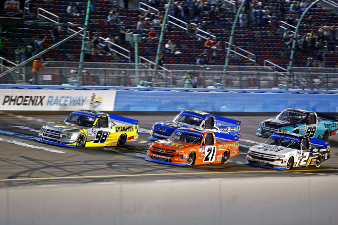 Grant Enfinger (98), Zane Smith (21), Brett Moffitt (23) and Sheldon Creed (2) lead the field during the start of the NASCAR Truck Series auto race at Phoenix Raceway, Friday, Nov. 6, 2020, in Avondale, Ariz. (AP Photo/Ralph Freso)