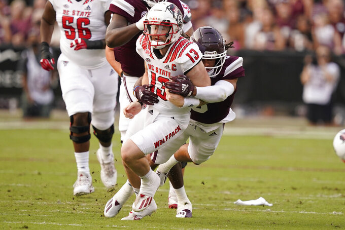 North Carolina State quarterback Devin Leary (13) is tackled by Mississippi State linebacker Aaron Brule (3) during the first half of an NCAA college football game in Starkville, Miss., Saturday, Sept. 11, 2021. (AP Photo/Rogelio V. Solis)