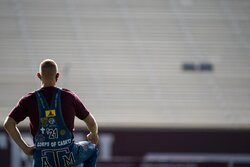 Texas A&M University Yell Leader Jacob Huffman takes a knee while looking over the empty stands at Kyle Field in College Station, Texas during the first Midnight Yell Practice this season early Saturday, Sept. 26, 2020. Due to Coronavirus restrictions, the Texas A&M Band were the only crowd allowed in the normally packed stands for the traditional game day event in College Station, Texas. (Sam Craft/Pool Photo via AP)