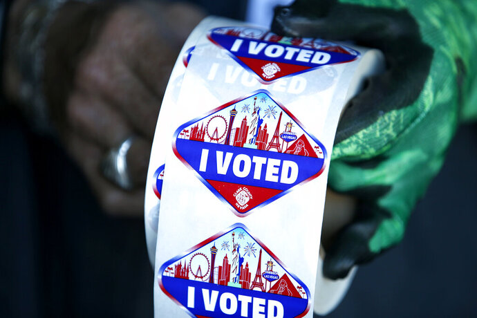 FILE - In this Saturday, Oct. 17, 2020, file photo a poll worker displays