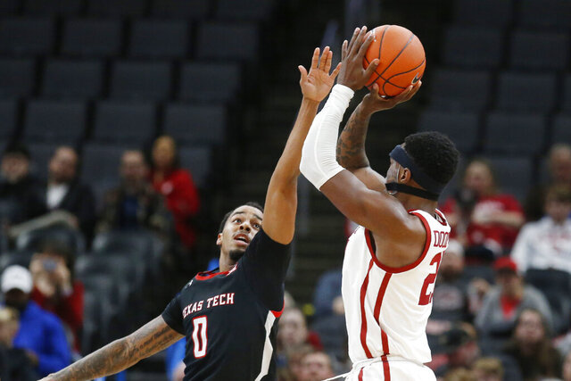 Oklahoma forward Kristian Doolittle, right, shoots over Texas Tech guard Kyler Edwards (0) in the second half of an NCAA college basketball game Tuesday, Feb. 25, 2020, in Oklahoma City. (AP Photo/Sue Ogrocki)