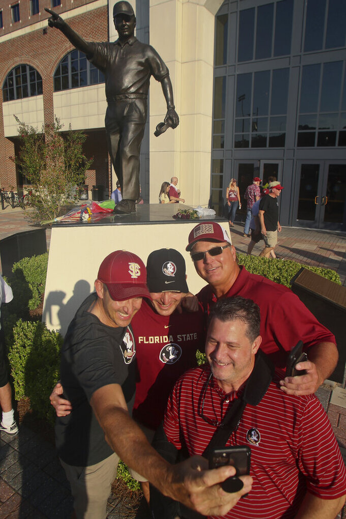 Friends take a photo in front of the statue of longtime Florida State football coach Bobby Bowden before an NCAA college football game against Notre Dame, Sunday, Sept. 5, 2021, in Tallahassee, Fla. Bowden passed away last month. (AP Photo/Phil Sears)