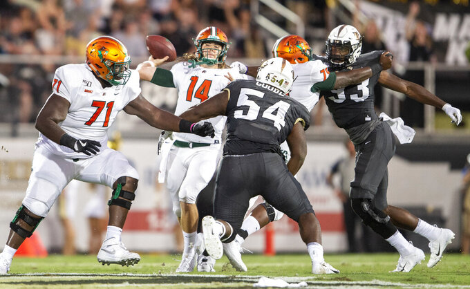 Florida A&M quarterback Ryan Stanley (14) throws a pass on Central Florida defensive linemen Cam Goode (54) and Landon Woodson (93) during the first half of an NCAA college football game Thursday, Aug. 29, 2019, in Orlando, Fla. (AP Photo/Willie J. Allen Jr.)