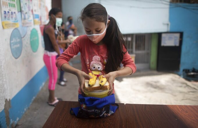 A girl wearing a protective face mask as a precaution against the new coronavirus places into her bag a pack-and-go lunch she received from a soup kitchen in the Petare neighborhood of Caracas, Venezuela, Wednesday, July 15, 2020, amid the new coronavirus pandemic. (AP Photo/Ariana Cubillos)