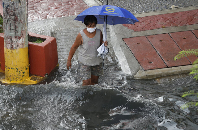 A woman wearing a protective mask to help prevent the spread of the new coronavirus crosses a flooded street during a brief downpour on Monday, June 15, 2020 in Manila, Philippines. (AP Photo/Aaron Favila)