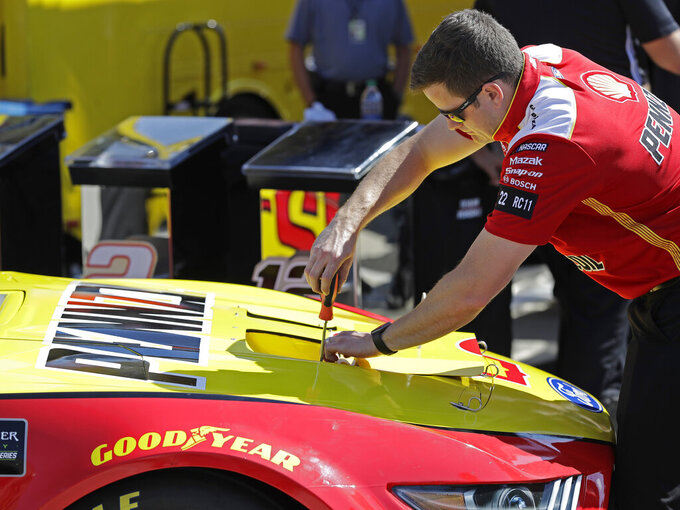 A crew member tightens radiator exit duct openings in the hood of Joey Logano's race car before qualifying for Saturday's NASCAR All-Star Cup series auto race at Charlotte Motor Speedway in Concord, N.C., Friday, May 17, 2019. NASCAR will be using the 2019 All-Star race at Charlotte Motor Speedway as a research and development project on how to improve their cars and create better and more exciting competition for next year. (AP Photo/Chuck Burton)