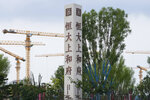 Construction cranes stand near the Evergrande's name and logo at its new housing development in Beijing, Wednesday, Sept. 15, 2021. One of China's biggest real estate developers is struggling to avoid defaulting on billions of dollars of debt, prompting concern about the broader economic impact and protests by apartment buyers about delays in completing projects. Rating agencies say Evergrande Group appears likely to be unable to repay all of the 572 billion yuan ($89 billion) it owes banks and other bondholders. That might jolt financial markets, but analysts say Beijing is likely to step in to prevent wider damage. (AP Photo/Andy Wong)