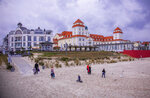 In this Saturday, May 23, 2020, some tourists stay on the beach in front of the Hotel Kurhaus Binz at the Baltic Sea island Ruegen in Binz, Germany. Germany's states, which determine their own coronavirus-related restrictions, have begun loosening lockdown rules to allow domestic tourists to return. ( Jens Buettner/dpa via AP)