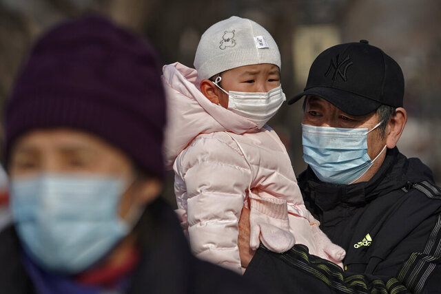 A man carries a child, both wearing face masks to help curb the spread of the coronavirus, as they stroll along a street near the popular frozen Houhai Lake in Beijing, Thursday, Jan. 21, 2021. China is making some of its toughest travel restrictions yet as coronavirus cases surge in several northern provinces ahead of the travel rush for Lunar New Year on next month. (AP Photo/Andy Wong)