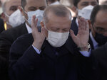 Turkey's President Recep Tayyip Erdogan prays as Turkish leaders, army commanders, family members and colleagues attend funeral prayers and a ceremony for 11 military personnel, including a high-ranking officer, at Ahmet Hamdi Akseki Mosque, in Ankara, Turkey, Friday, March 5, 2021. Turkish army officers were killed on Thursday when an army helicopter crashed in a snow-covered mountainous area in Bitlis, eastern Turkey. (AP Photo/Burhan Ozbilici)