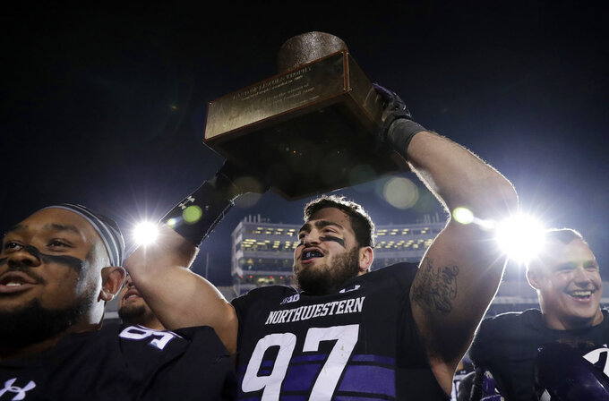 Northwestern defensive line Joe Gaziano, center, celebrates with teammates as he holds the Land of Lincoln Trophy after Northwestern defeated Illinois 24-16 in an NCAA college football game in Evanston, Ill., Saturday, Nov. 24, 2018. (AP Photo/Nam Y. Huh)