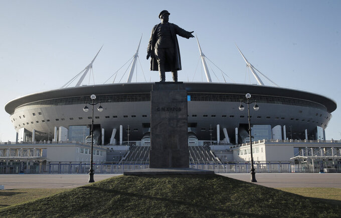 A sculpture of one of Bolshevik's leader Sergei Kirov stands in font of the Saint-Petersburg Arena in St.Petersburg, Russia Tuesday, Feb. 4, 2020. With coronavirus restrictions eased to allow fans back into stadiums, there at least will be some atmosphere at the tournament after months of games being played without any. Budapest wants all fans to come, while Saint Petersburg and Baku hope to use 50% of stadium capacity. (AP Photo/Dmitri Lovetsky)