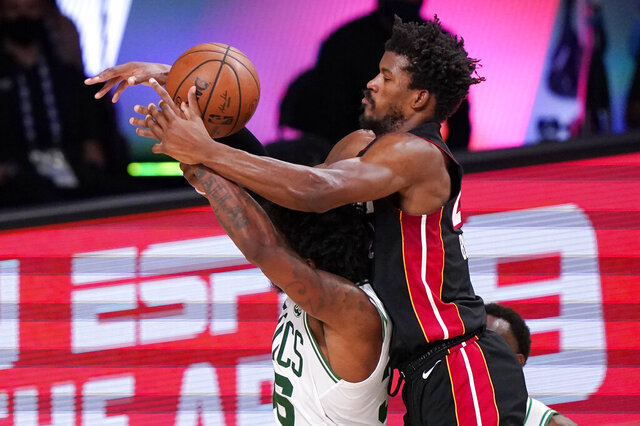 Miami Heat's Jimmy Butler, right, goes over the top of Boston Celtics' Marcus Smart (36) during the second half of an NBA conference final playoff basketball game Sunday, Sept. 27, 2020, in Lake Buena Vista, Fla. (AP Photo/Mark J. Terrill)