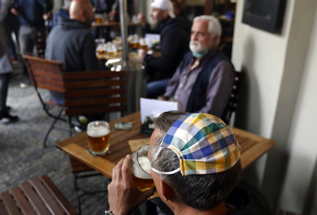 A man, wearing his face mask on top of his head, drinks a beer at a restaurant terrace in Prague, Czech Republic, Monday, May 11, 2020.Bars, restaurants, cafes offering outdoor seating started to serve their first consumers since March 14, as the Czech Republic is taking a step to normalcy amid the coronavirus pandemic by easing more restrictions adopted by the government to contain it. Interiors of the restaurants still remain closed. (AP Photo/Petr David Josek)