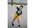 In this Aug. 16, 2018, photo, a boy launches a football in the Lambeau Field parking lot before a preseason NFL football game between the Green Bay Packers and the Pittsburgh Steelers in Green Bay, Wis. USA Football has unveiled a council that will oversee the implementation of its Football Development Model for the sport to help parents, coaches and program leaders provide what players need to develop and grow as athletes and people through football participation. (AP Photo/Jeffrey Phelps)