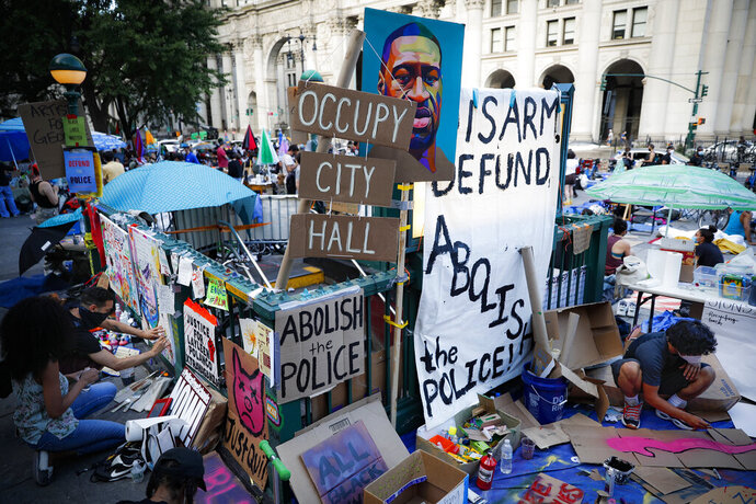 Protesters plaster signs and artwork on a subway entrance as they gather at an encampment outside City Hall, Friday, June 26, 2020, in New York. (AP Photo/John Minchillo)