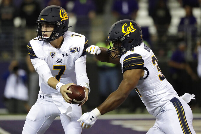 California quarterback Chase Garbers, left, hands off to running back Christopher Brown Jr., right, during the first half of an NCAA college football game Saturday, Sept. 7, 2019, in Seattle. (AP Photo/Ted S. Warren)