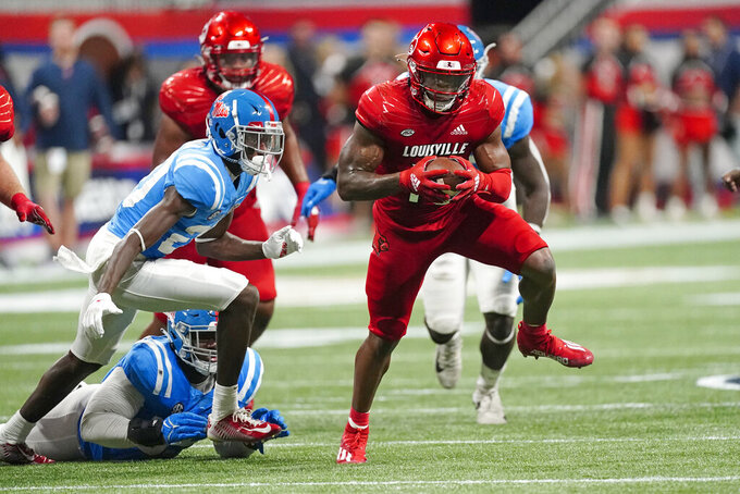 Louisville running back Jalen Mitchell (15) runs past Mississippi defensive back Keidron Smith (20) during the second half of an NCAA college football game Monday, Sept. 6, 2021, in Atlanta. (AP Photo/John Bazemore)