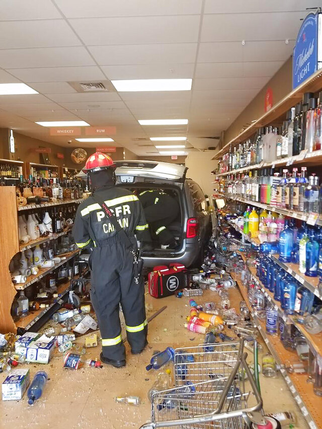 In a photo provided by the Dade City Police Department, Dade City police work at the site where officials say a minivan crashed into a Publix liquor store in Florida, injuring an employee and a customer and leaving many broken bottles. The Tampa Bay Times reports an elderly woman left the parking area and jumped a curb and kept going for another 24 feet before striking the entrance and fully entering the Dade City store. (Dade City Police Department via AP)