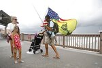 """Michael Taylor, also known as """"The Armed Fisherman"""" ties a fishing knot while at Pier 60,  in Clearwater Beach, Fla.,  with his 2-year-old daughter Ocean and his assault rifle and fishing gear, on Saturday, July 3, 2021. (Octavio Jones/Tampa Bay Times via AP)"""