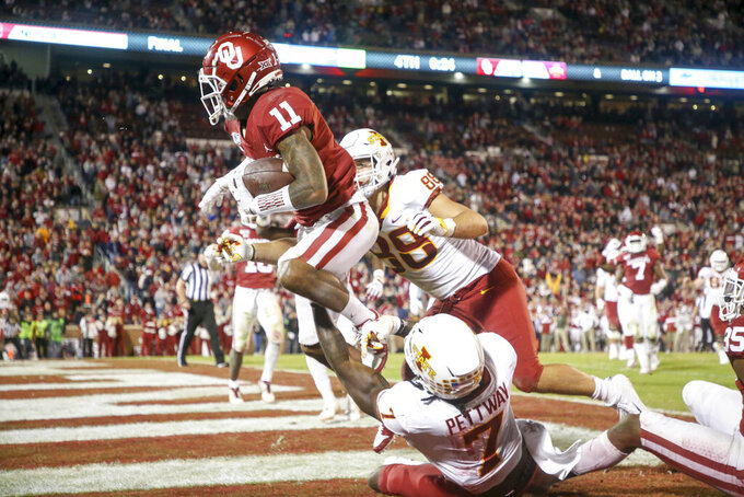 Oklahoma Sooners cornerback Parnell Motley (11) intercepts a pass intended for Iowa State Cyclones wide receiver La'Michael Pettway (7) during the NCAA football game between the against the Iowa State Cyclones and the Oklahoma Sooners at Gaylord Family-Oklahoma Memorial Stadium in Norman, Okla., on Saturday, Nov. 9, 2019. (Ian Maule/Tulsa World via AP)